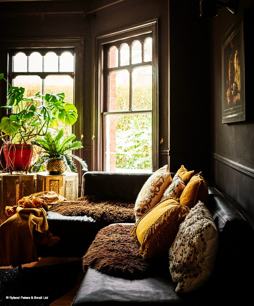 The living room of Rockett St George Co-Founder Lucy St George with dark painted walls, house plants and yellow cushions and image by Catherine Gratwicke
