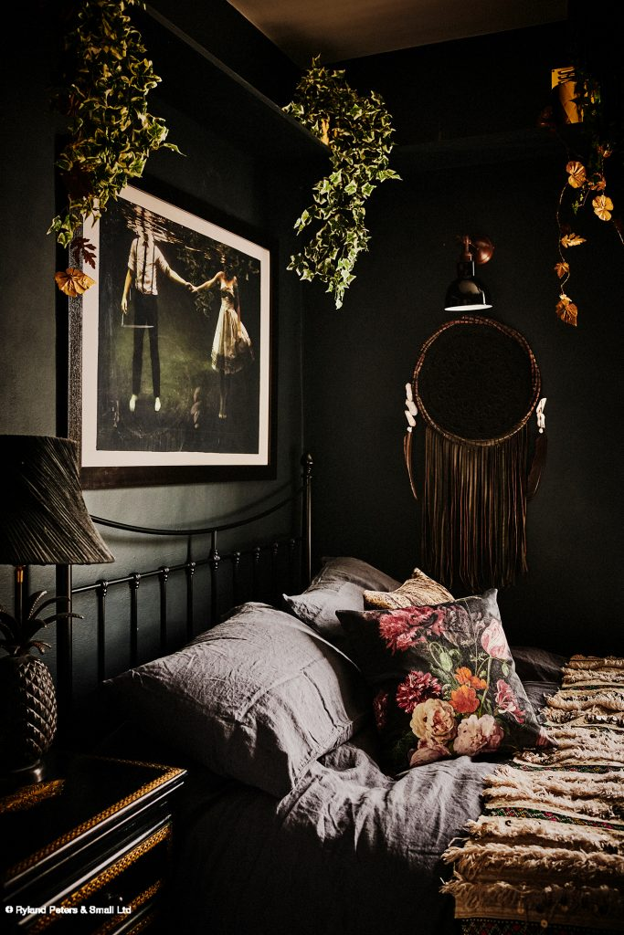 The dark painted bedroom of Lucy St George, Co-Founder of Rockett St George with art work and floral cushion image by Catherine Gratwick