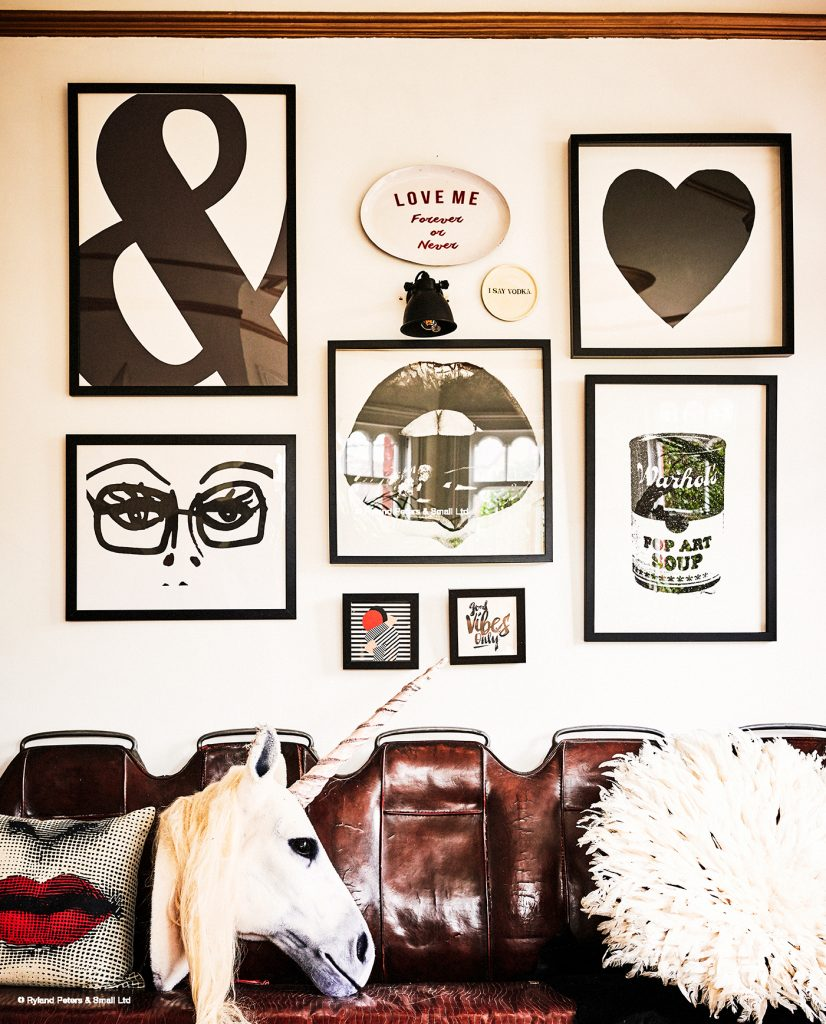 The gallery wall in the study of Co-Founder of Rockett St George, Lucy St George, with monochrome prints and vintage furniture