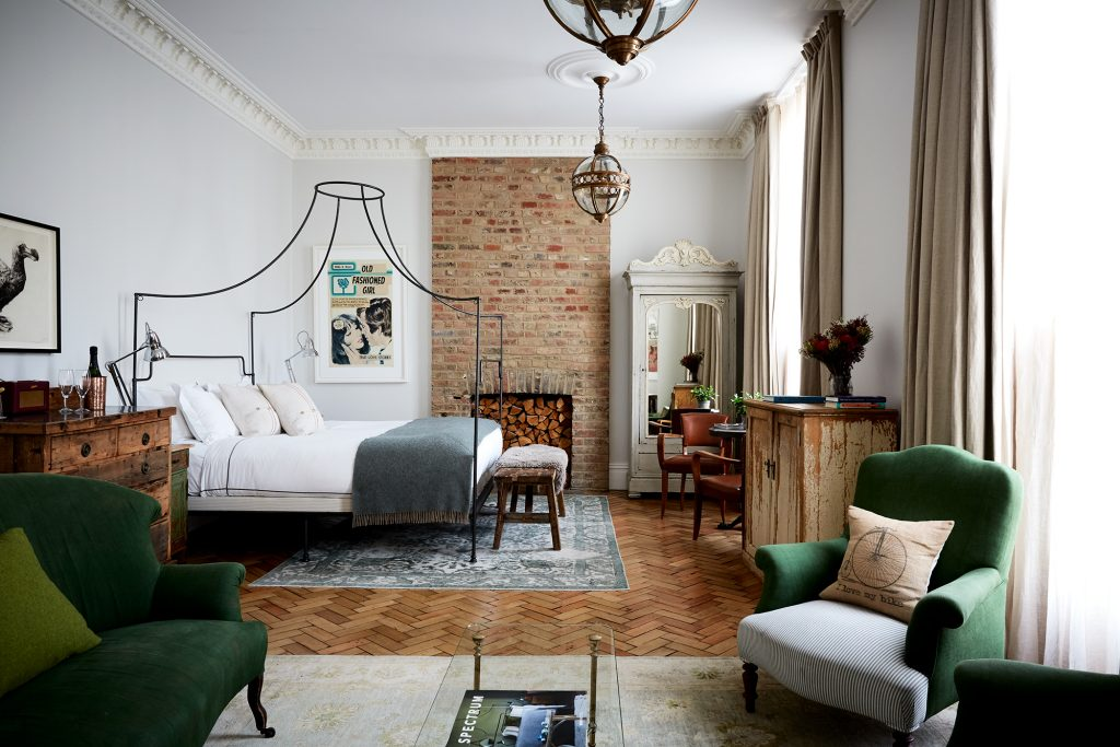 The Grand Suite in Artist Residence hotel in Pimlico London with its wrought iron bed and green sofa