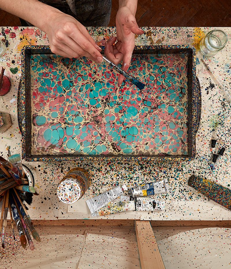 Lucy McGrath founder of Marmor Paperie marbling at her studio at Cockpit Arts, flatlay image featuring paint brushes, paints, pipettes, jars and splatter effect
