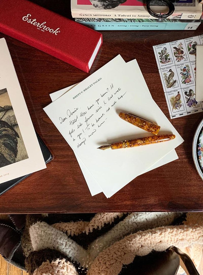 Flatlay of letter writing on a desk featuring pen and paper, by Brett Braley-Palko