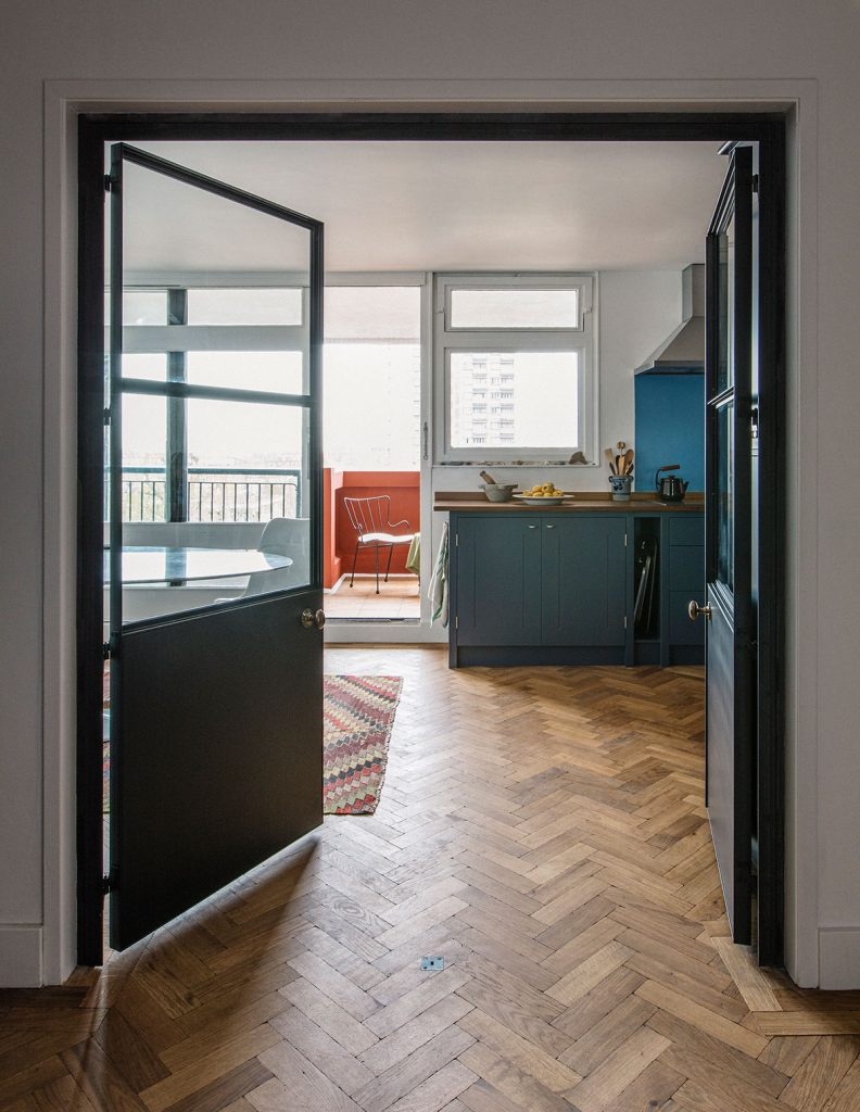 Glass door leading to British Standard Kitchen in blue with parquet wood flooring