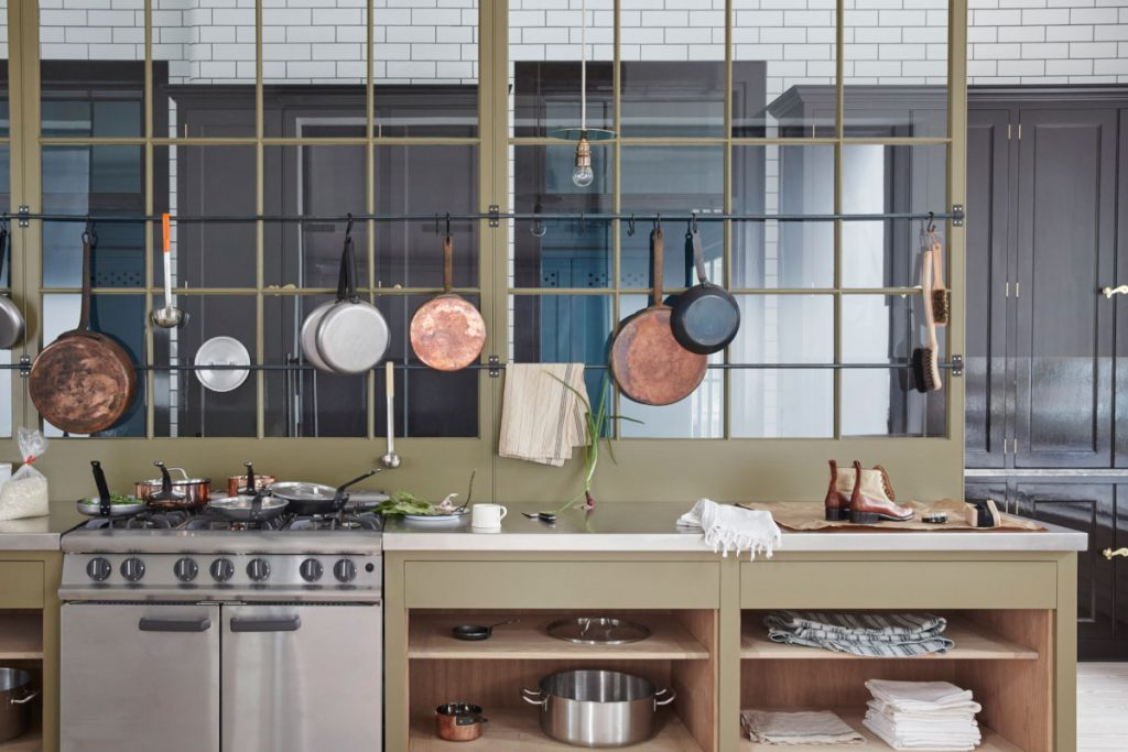Olive green glass panels hung with copper pans in the kitchen, designed by Plain English