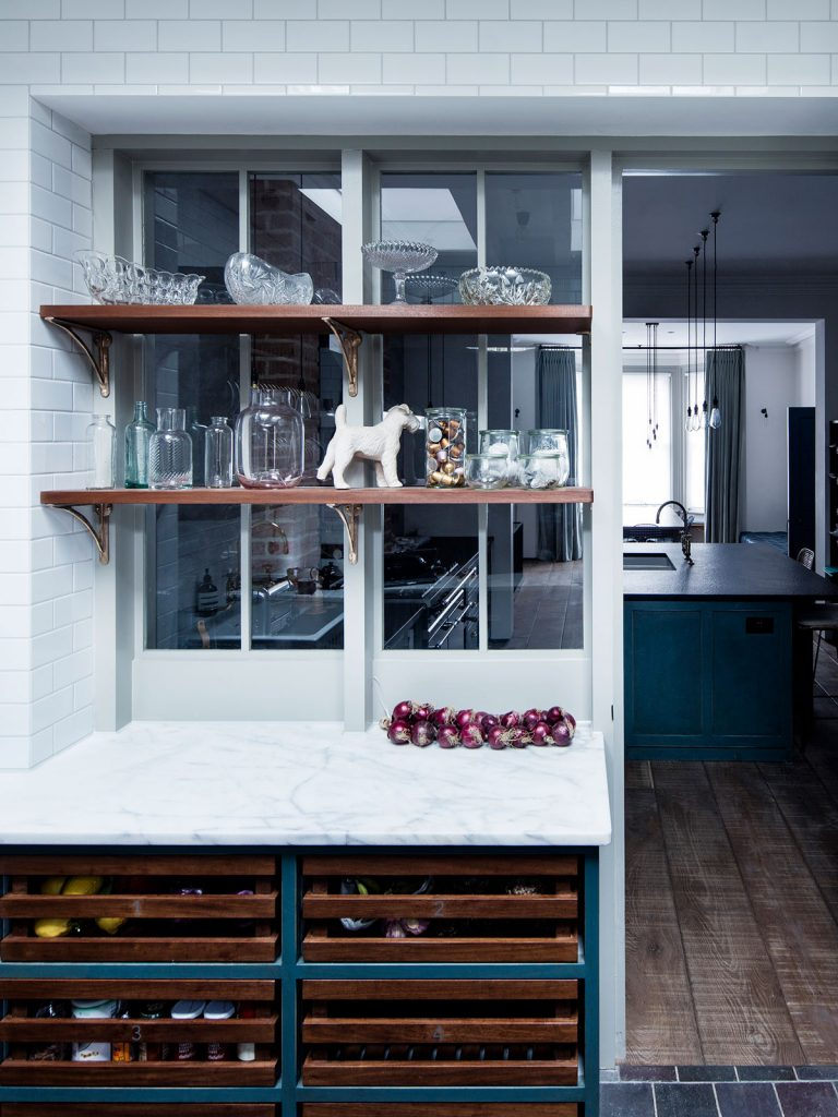 Glass panels featuring shelving and glassware overlooking the kitchen at the home of Mark Lewis, photograph by Rory Gardiner