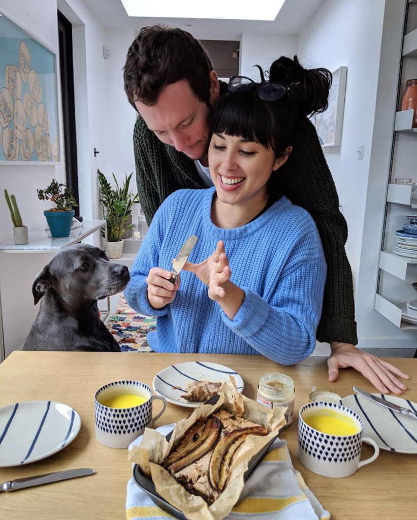 Melissa Hemsley at home at her dining table with boyfriend Henry and their Staffordshire bull terrier Nelly. Instagram
