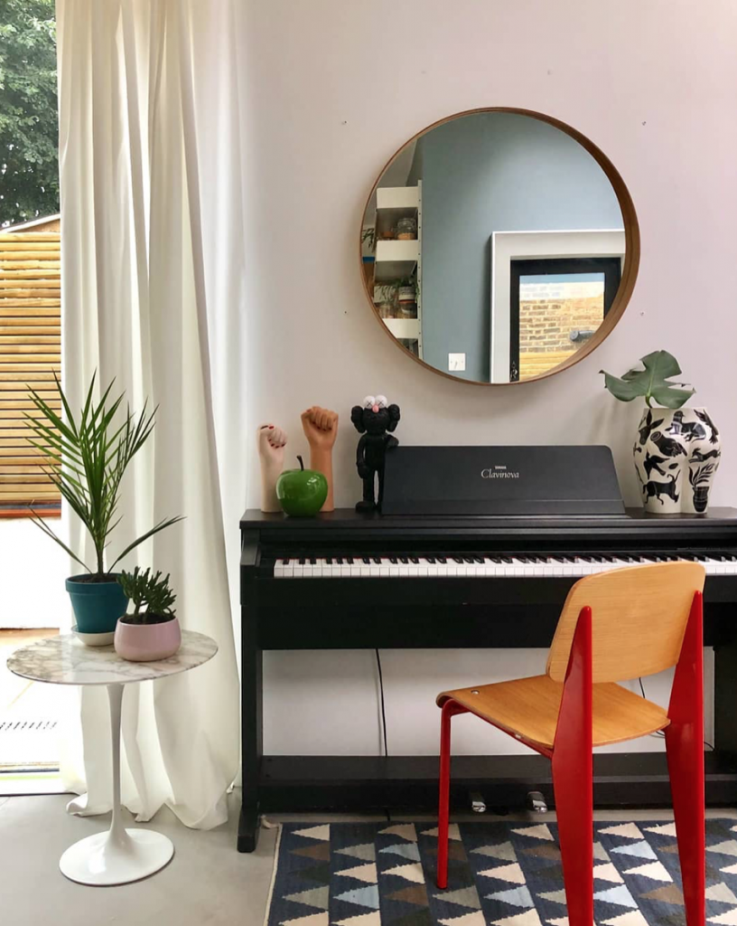 Electric piano with round mirror, pink wall, marble side table and red chair at the home of Melissa Hemsley. Instagram