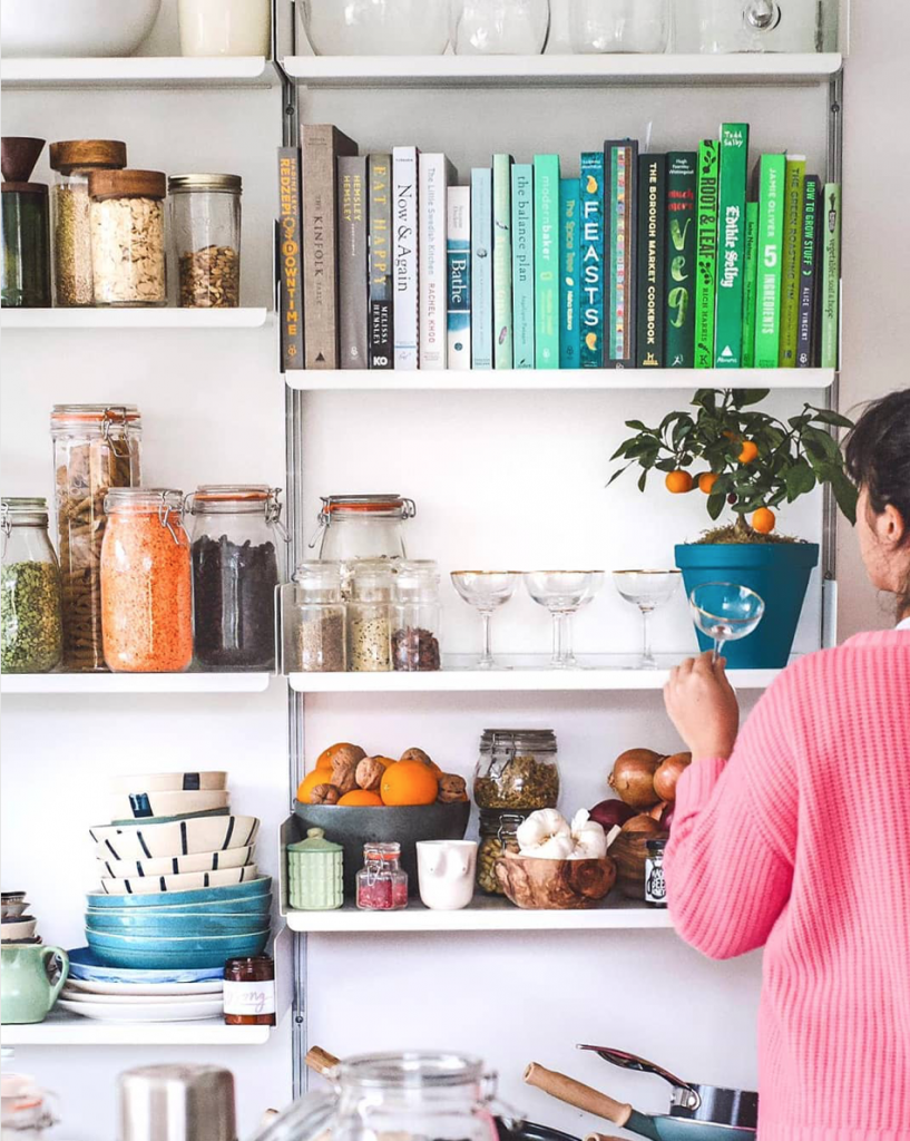 Open shelving with kilner jars and storage jars of pulses and grains, cookbooks and servewear at the home of Melissa Hemsley. Instagram.
