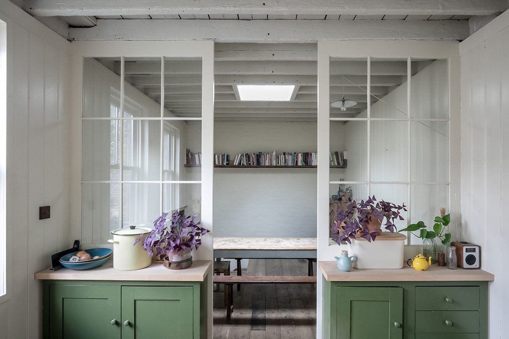 Green kitchen units, white weatherboard walls and glass panels between kitchen and dining area at The Coach House, marketed by The Modern House
