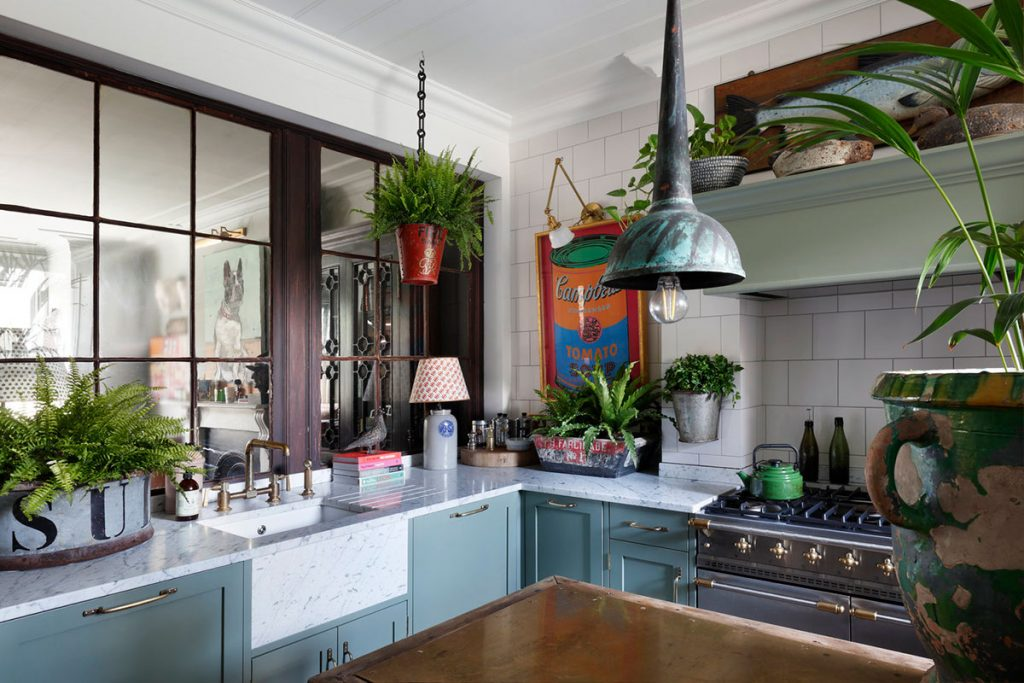 The kitchen featuring traditional shaker units, antiques and greenery - at the home of Tom Cox of ham interiors