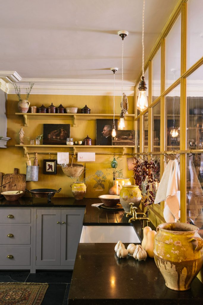 Ochre kitchen with grey cabinets and glass panelling in the deVOL New York showroom