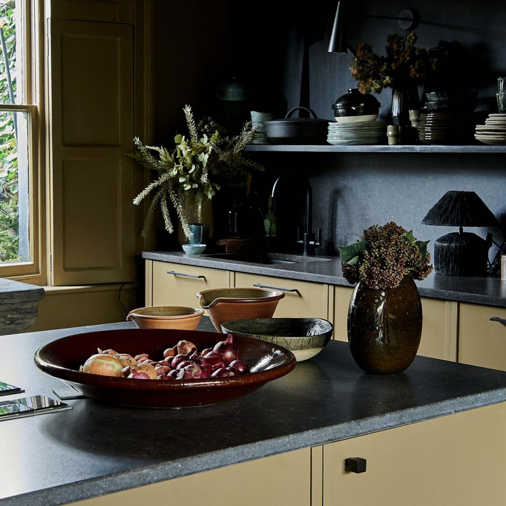 Black work surfaces and stoneware in the kitchen of designer Abigail Ahern in East London