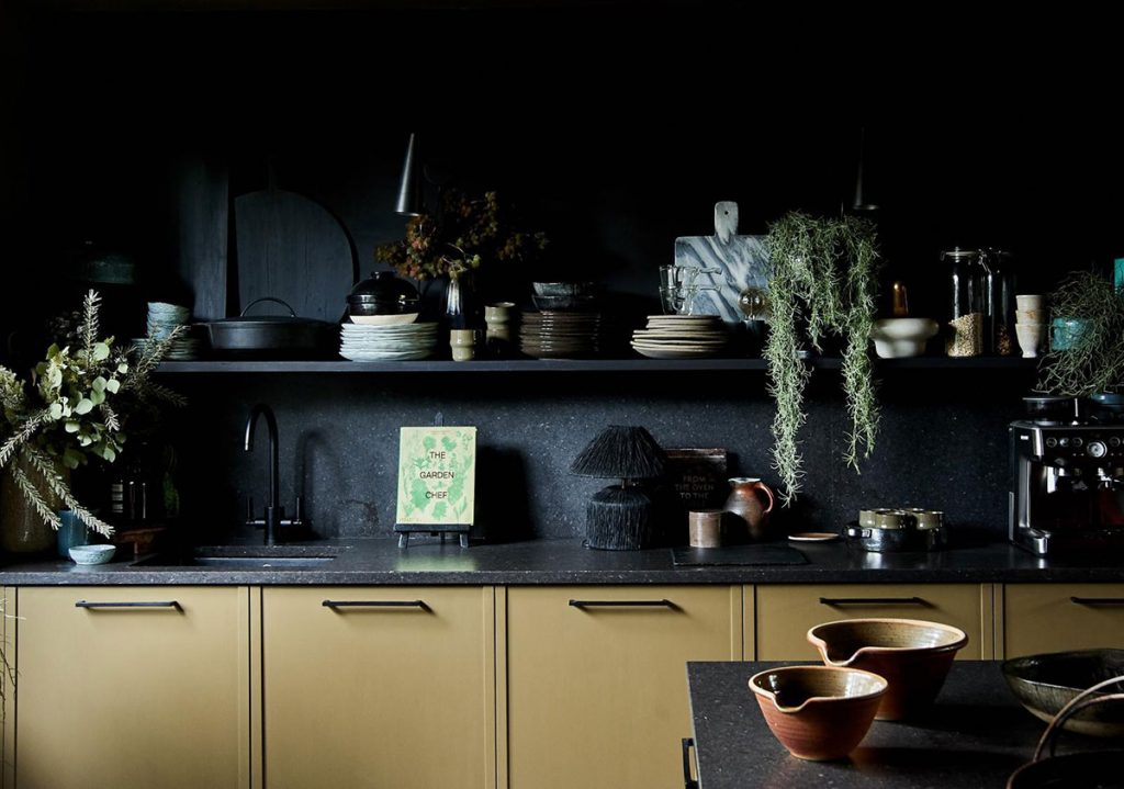 Black walls and open shelving in kitchen of Abigail Ahern, by Herringbone Kitchens