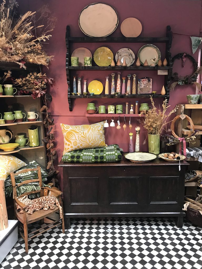Ceramics, cushions, antique chest and shelving at Collate Interiors in Axminster