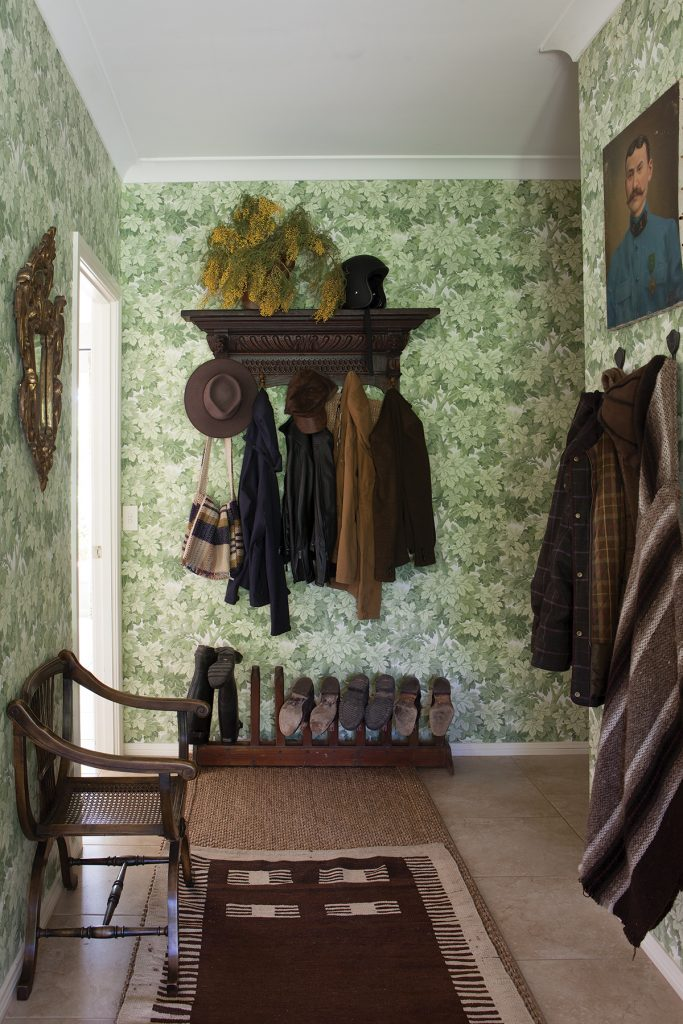 Green leaf wallpaper and dark wood furniture in the entrance hall at the home of Designer Lisa Burdus, photographer Simon Griffiths, from Australian Designers at Home by Jenny Rose-Innes