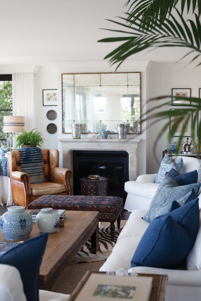 White walls, marble fireplace, blue textiles and greenery in the living room of designer Lynda Kerry, Photographer Simon Griffiths, from Australian Designers at Home by Jenny Rose-Innes