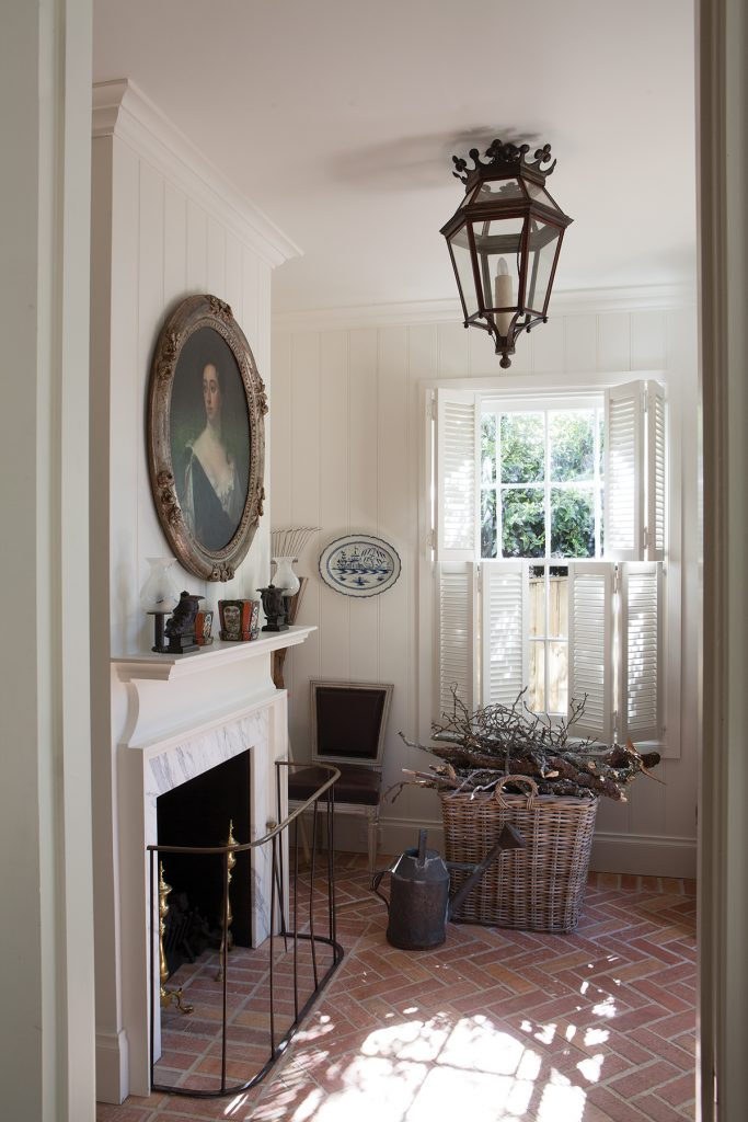 White fireplace, herringbone brick floor, window shutters and antiques in the home of designer Cameron Kimber, Photographer Simon Griffiths, from Australian Designers at Home by Jenny Rose-Innes