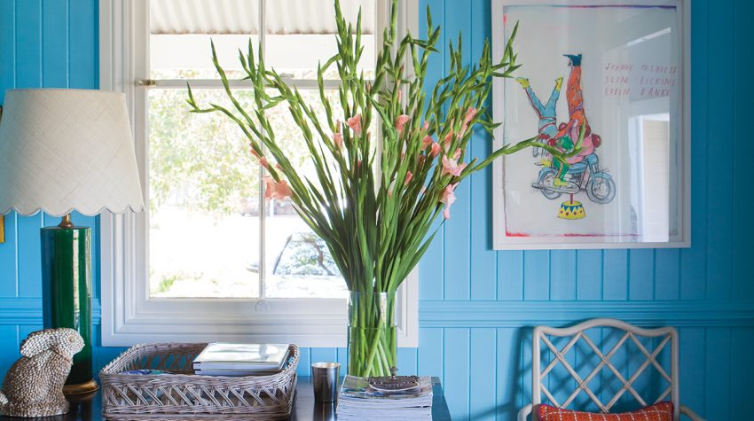 Bright blue weatherboard walls, beautiful window, flowers, antique desk and green upholstered chairs in the home of designer Anna Spiro, from Australian Designers at Home by Jenny Rose-Innes