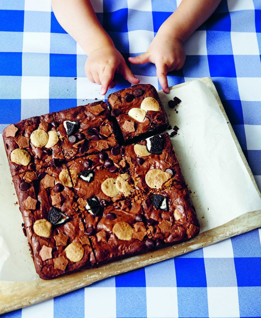 Little boy reaching for a serving board filled with Triple Threat Chocolate Brownies from Table Manners with Jessie Ware cookbook