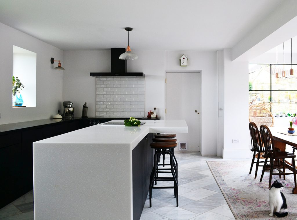 white and dark blue open plan kitchen diner at the home of Amy Hemmings-Batt, Founder of Coco and Wolf, Somerset, UK