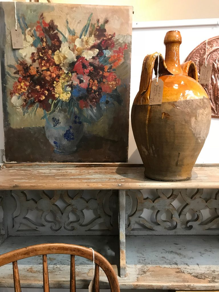 An oil painting of flowers in a vase and a vintage glazed pot at Petworth Antiques Market