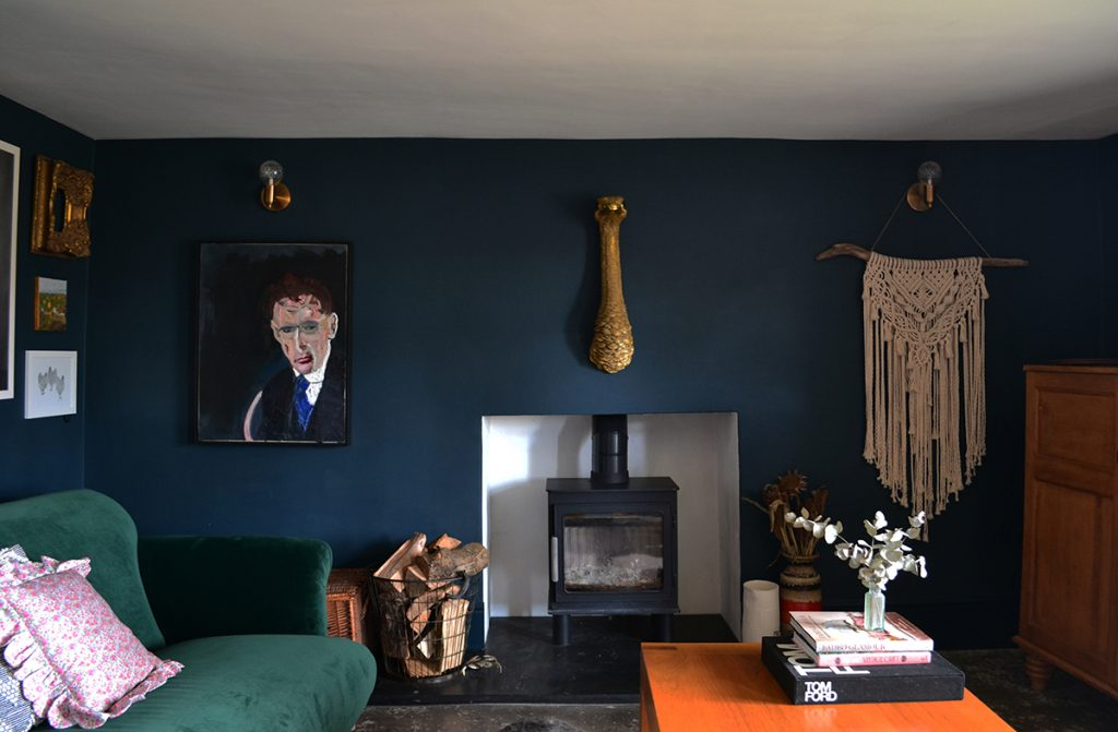 Farrow & Ball Hague Blue walls, log burner and wall hangings in the living room of Amy Hemmings-Batt, Founder of Coco and Wolf, Somerset, UK