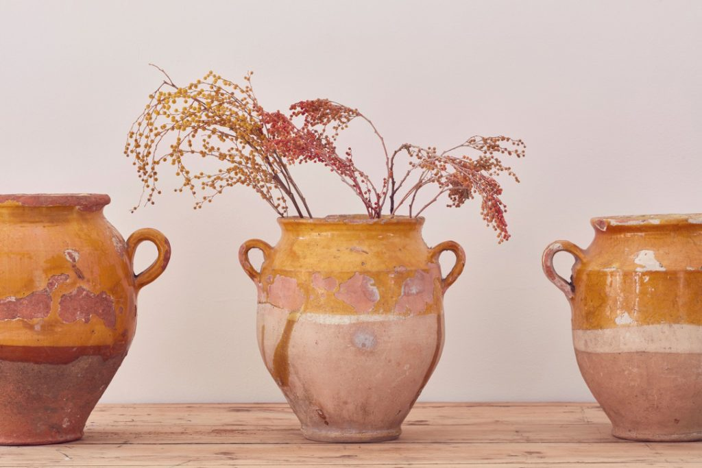 Foliage in rustic antique stoneware urns in terracotta glaze from Home Barn vintage furniture and homeware store in Marlow, Buckinghamshire