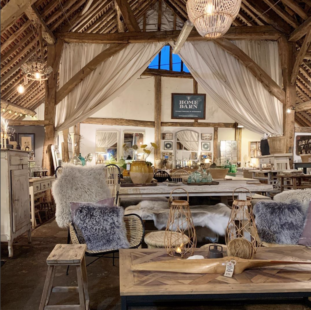 sheepskin throws, wicker chairs, reclaimed wooden coffee table, vintage stool at Home Barn vintage furniture and homeware store in Marlow, Buckinghamshire