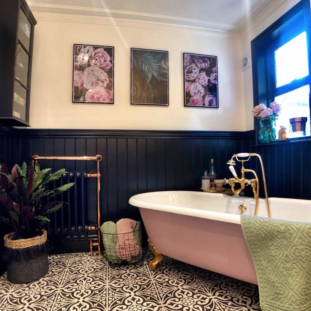 Laura Cave's bathroom with pink freestanding bath, black and white for tiles, dark wood panelling and botanical prints restored after the fire 2019