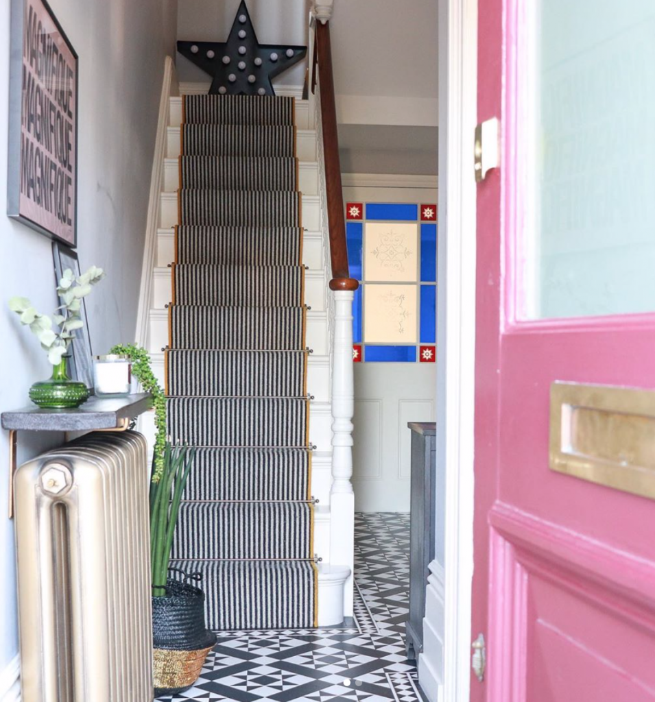 Laura Cave's hallway with monochrome tiled floor, pink front door, striped sir runner and reclaimed Victorian radiator restored after the fire 2019