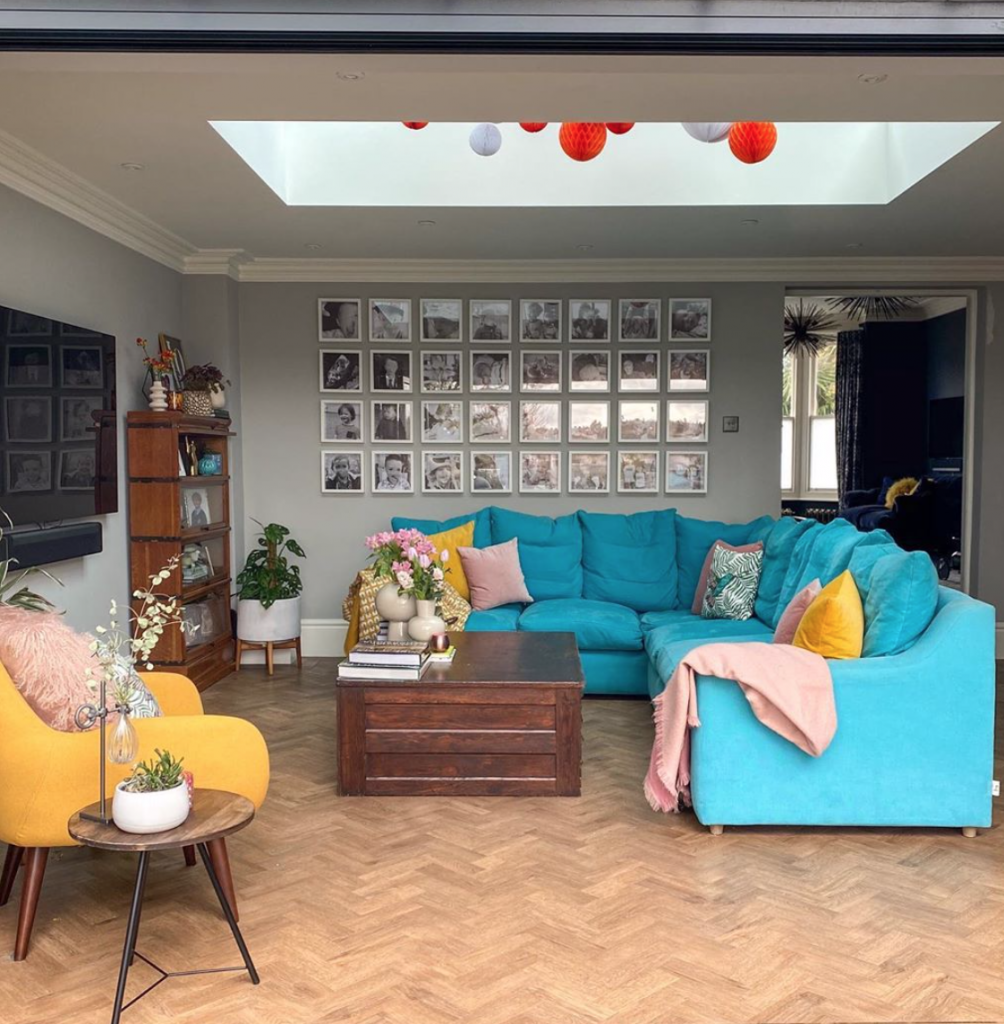Laura Cave's living room with blue corner sofa, gallery wall, parquet flooring and ceiling lantern restored after the fire 2019