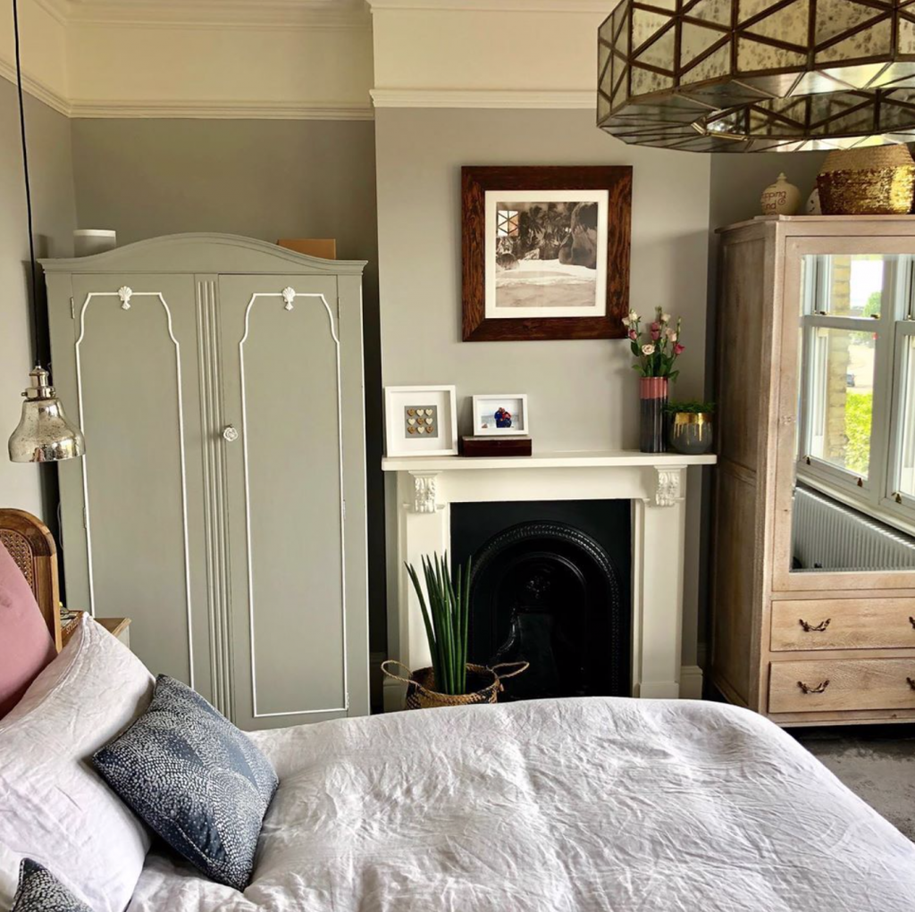 Laura Cave's master bedroom with sage green walls, Victorian fireplace, wooden wardrobe and smoked glass ceiling light restored after the fire 2019