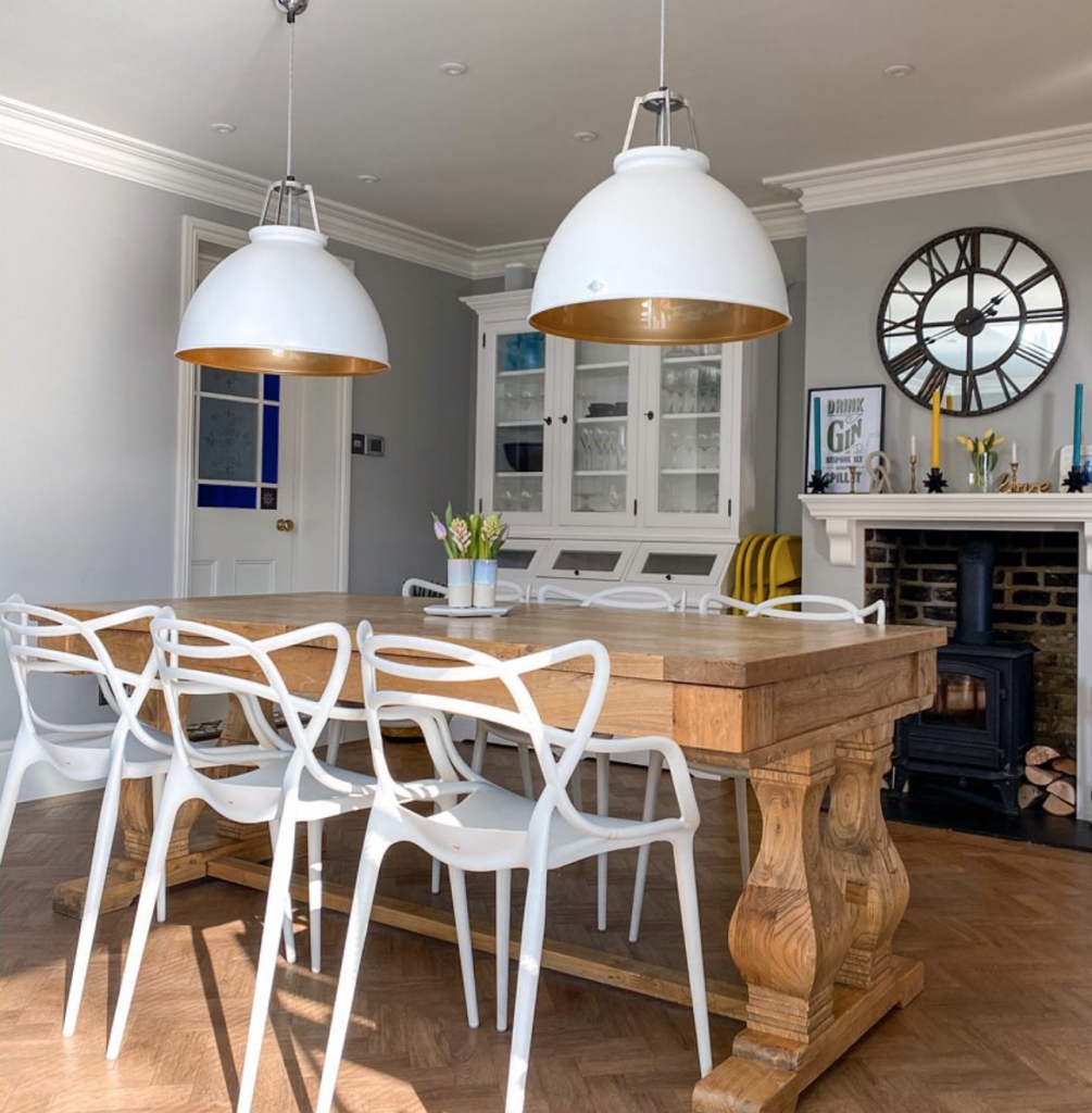 Laura Cave light grey dining room with wooden dining table, Kartell chairs and giant pendant lights restored after the fire 2019