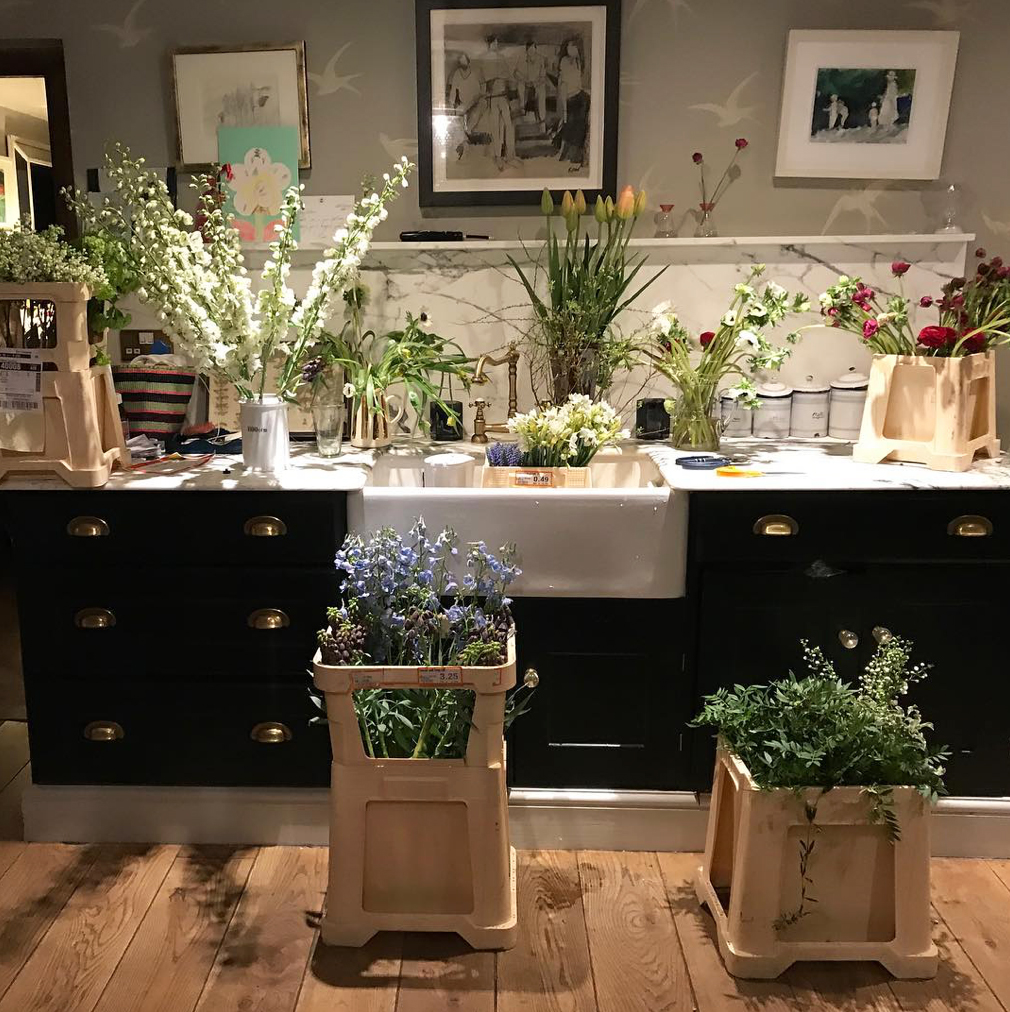 Vases and containers of flowers fill the work surfaces in the kitchen of florist and author Willow Crossley at her home in the Cotswolds