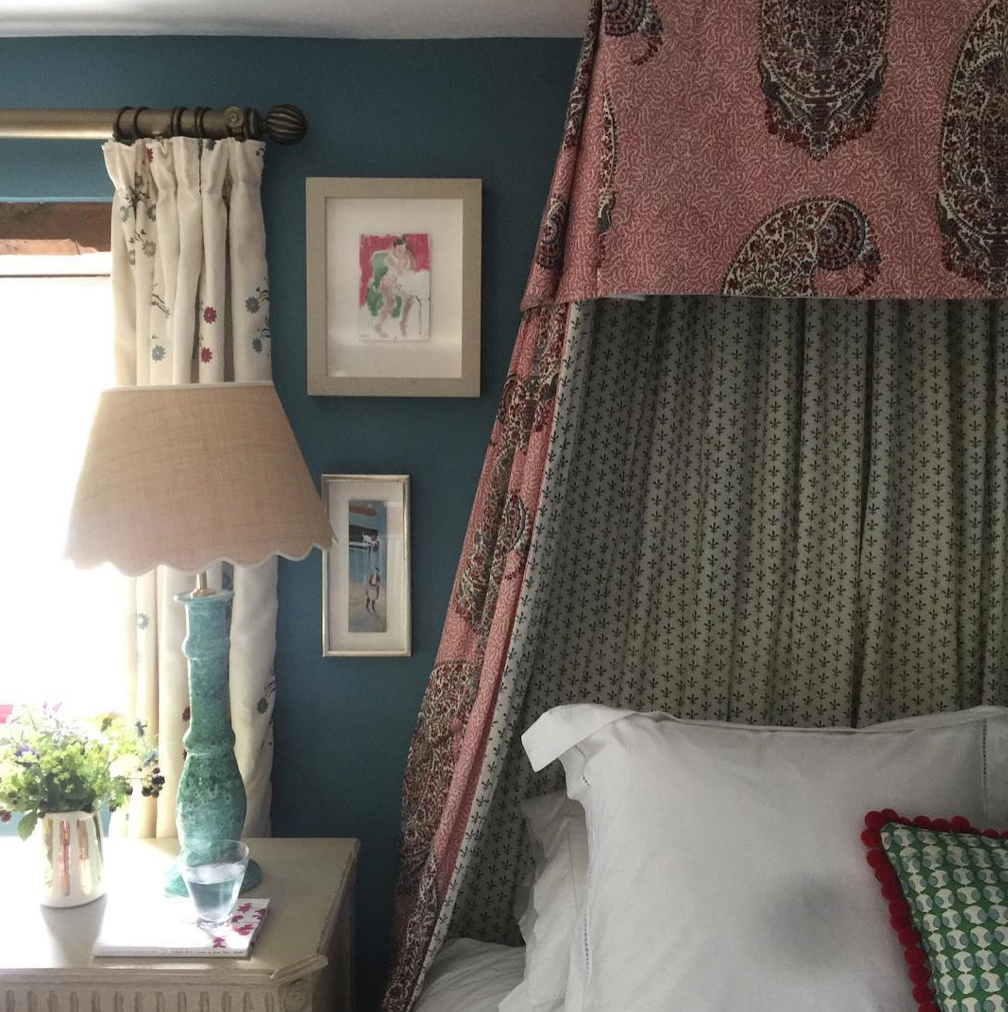 Florist and author Willow Crossley's bedroom at her home in the Cotswolds with Matilda Goad lampshade, floral fabric canopy above bed, art on dark blue walls and flowers on bedside table