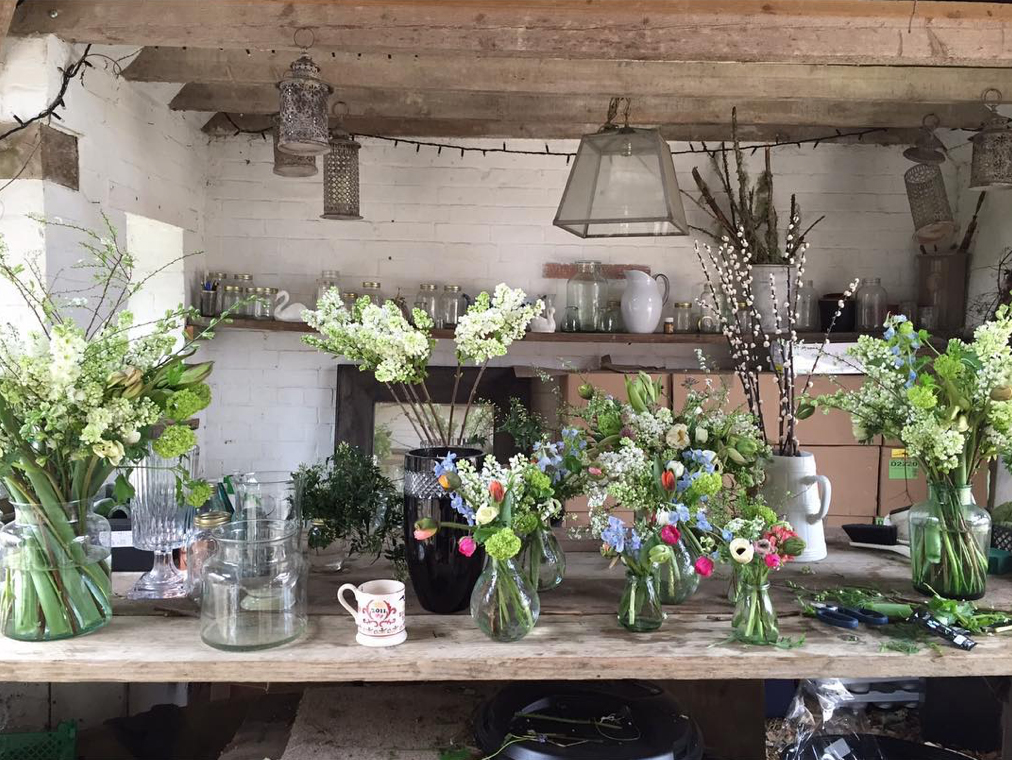 Flower stylist Willow Crossley's flower studio in an outhouse at her home in the Cotswolds featuring rustic wood table, jugs and vases of flowers, hanging glass lantern pendant, jug of pussy willow