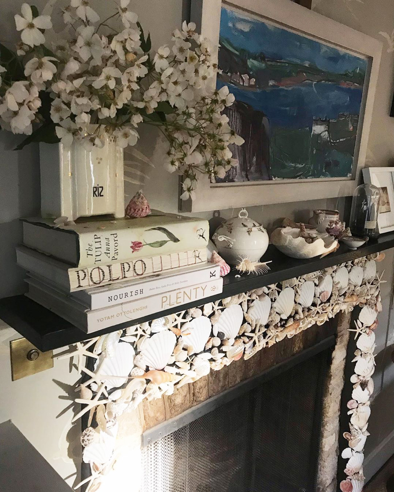 Willow Crossley's fireplace at her home in the Cotswolds, decorated with shells and with cookbooks, flowers and shells on mantelpiece