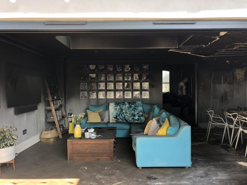 Laura Cave's living room with blue corner sofa and gallery wall damaged by the electrical house fire in 2018