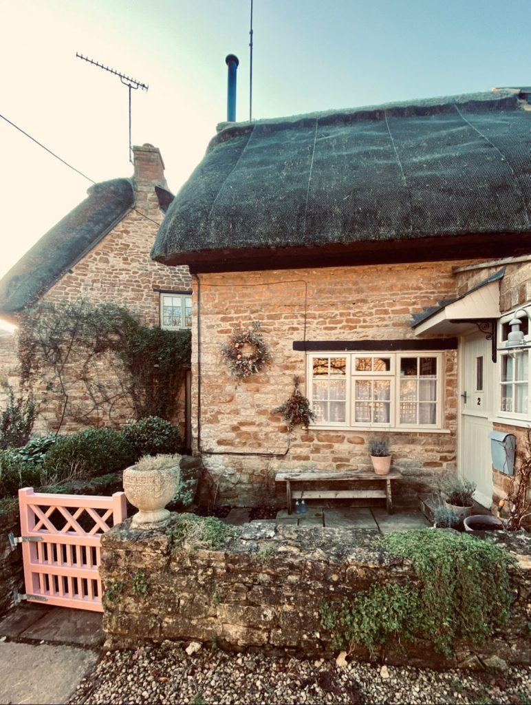 pretty thatched Cotswolds stone cottage and pink gate, the home of interior designer Victoria Barker, founder of Studio Faeger