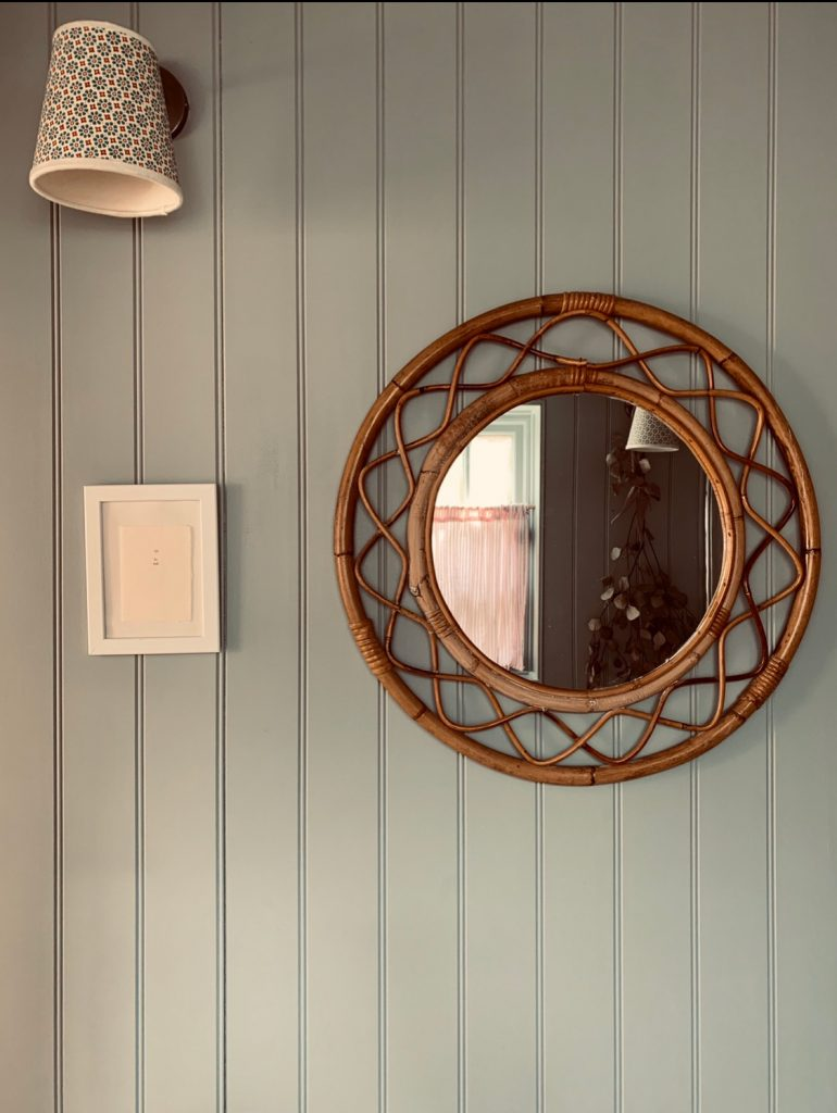 wicker framed wall mirror and wall light on shiplap wall in the Cotswolds home of interior designer Victoria Barker, founder of Studio Faeger