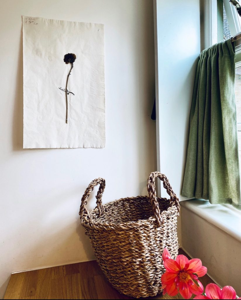 pressed flower hanging on wall above wicker basket in the Cotswolds home of interior designer Victoria Barker, founder of Studio Faeger