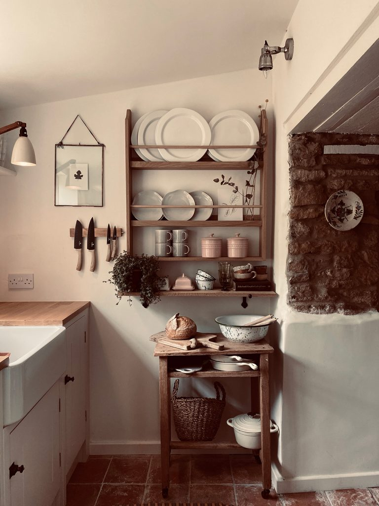 wooden plat rack, butlers sink and stone floor in country cottage kitchen in the Cotswolds home of interior designer Victoria Barker, founder of Studio Faeger