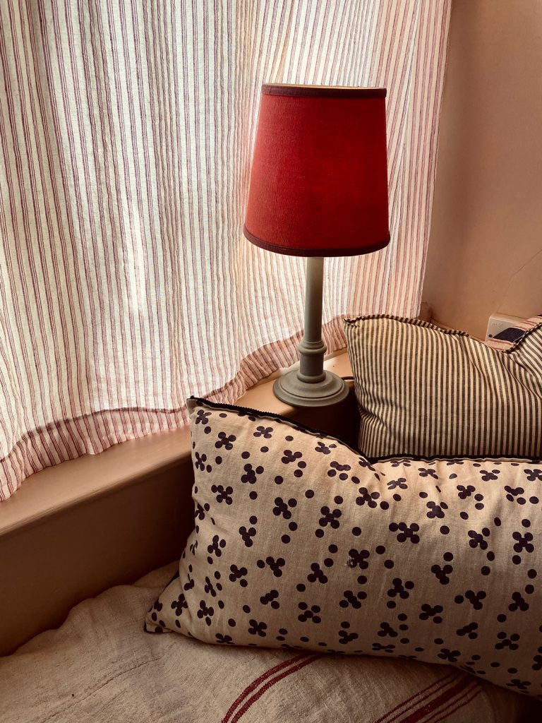 table lamp with red lampshade, ticking stripe curtain and cushions in the Cotswolds home of interior designer Victoria Barker, founder of Studio Faeger