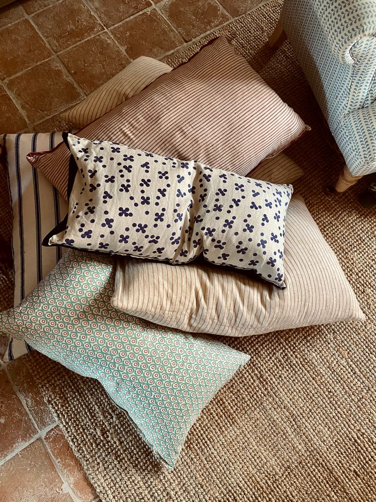 scatter cushions on sisal rug on flagstone floor in the Cotswolds home of interior designer Victoria Barker, founder of Studio Faeger