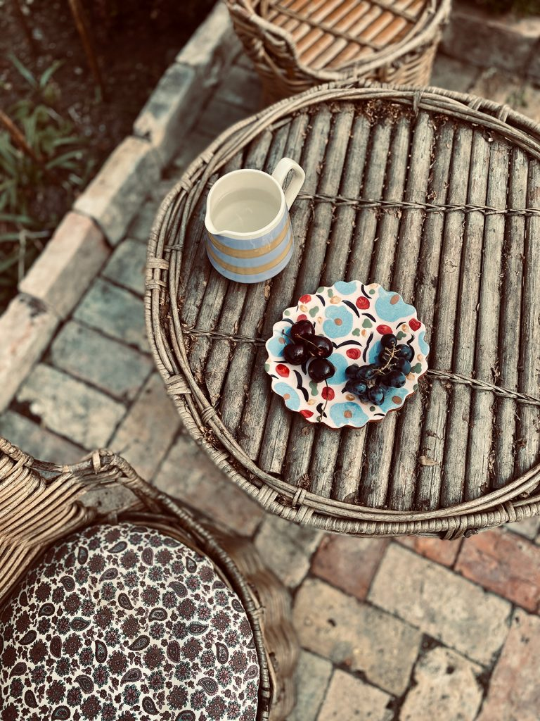 wicker patio furniture with Rachael Cocker plate and jug in the Cotswolds home of interior designer Victoria Barker, founder of Studio Faeger