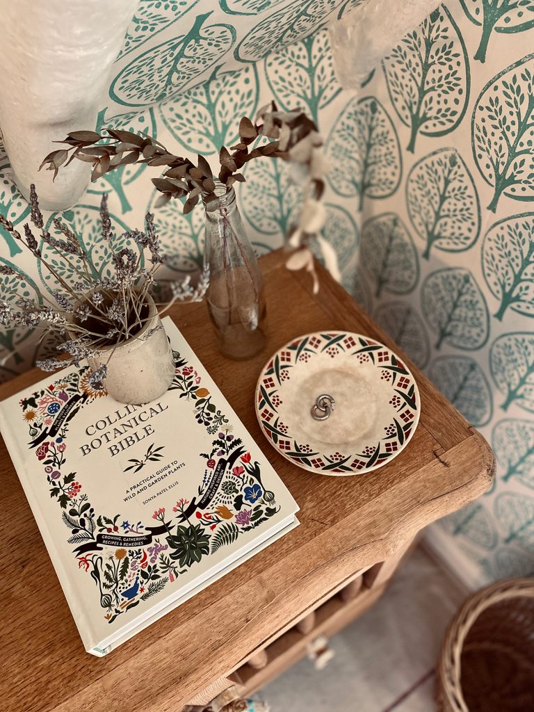 wooden bedside table with jars of dried flowers, botanical bible book and pretty jewellery dish in the Cotswolds home of interior designer Victoria Barker, founder of Studio Faeger