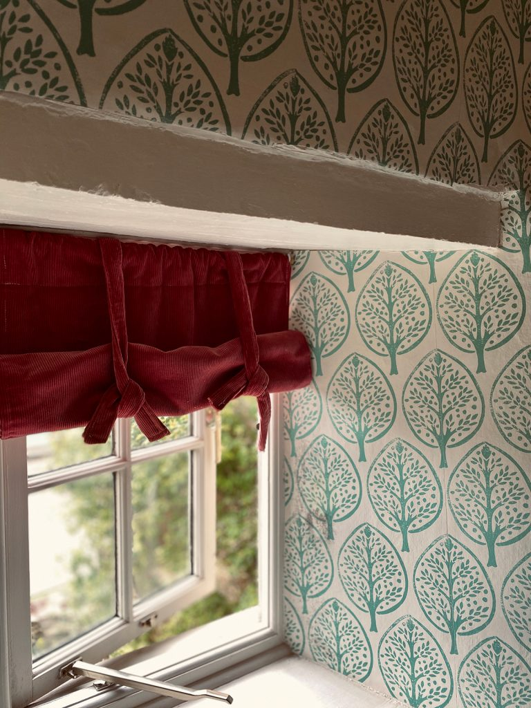 red corduroy window blind and Molly Mahon leaf wallpaper in the Cotswolds home of interior designer Victoria Barker, founder of Studio Faeger
