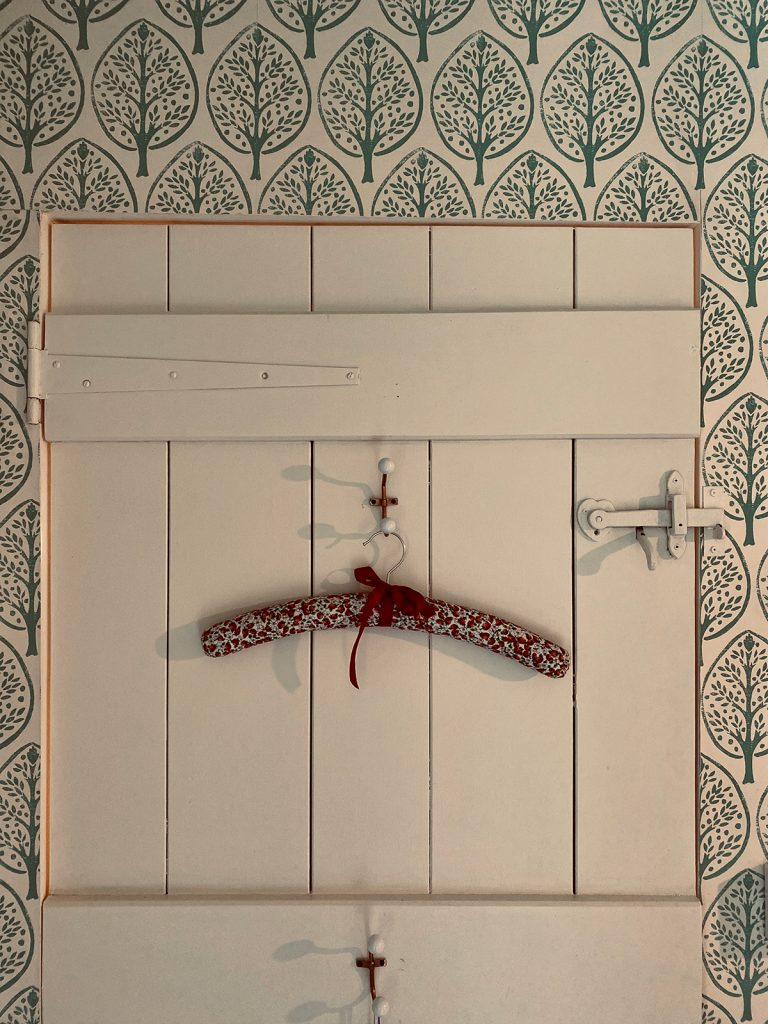 pretty floral coat hanger on the back of wooden cottage door in the Cotswolds home of interior designer Victoria Barker, founder of Studio Faeger