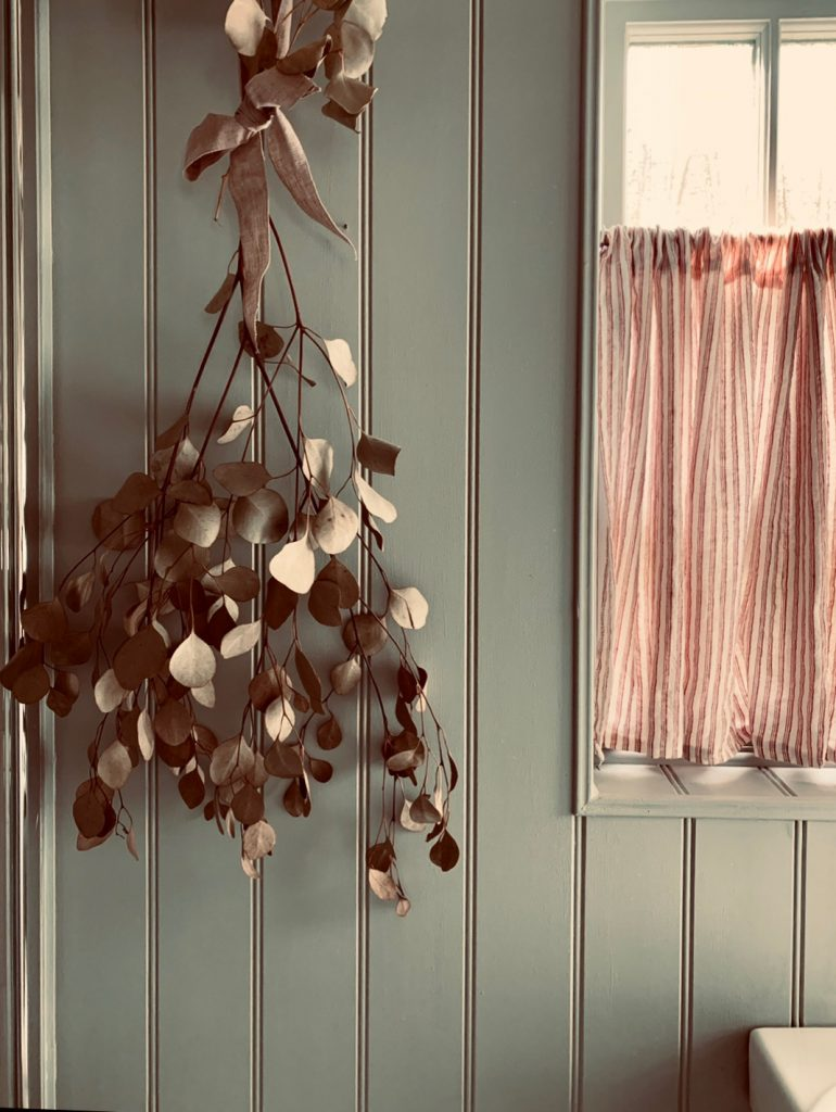 dried handing eucalyptus and ticking stripe curtain in the Cotswolds home of interior designer Victoria Barker, founder of Studio Faeger