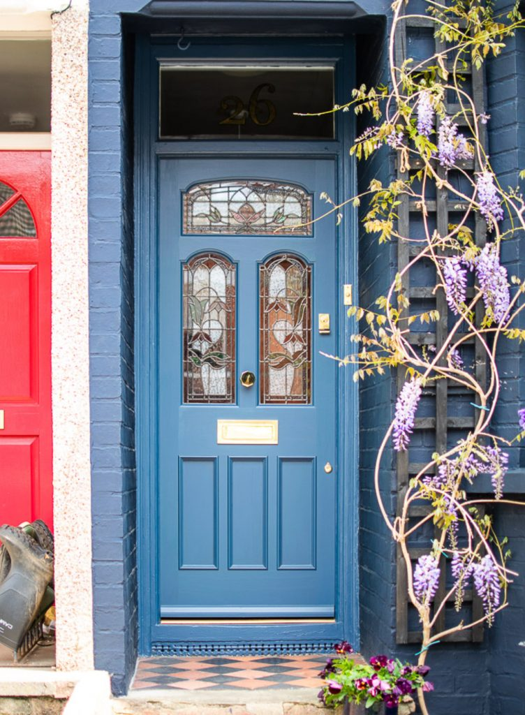 Blue front door with stained glass panelling and wisteria around door. By Cotswood doors